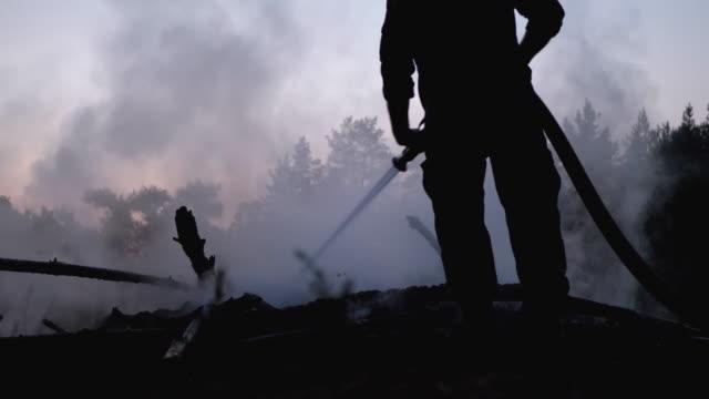 släck eld med vatten genom firehose. brandman håller slang och släcka skogs lägerelden på kvällen - skog brand bildbanksvideor och videomaterial från bakom kulisserna