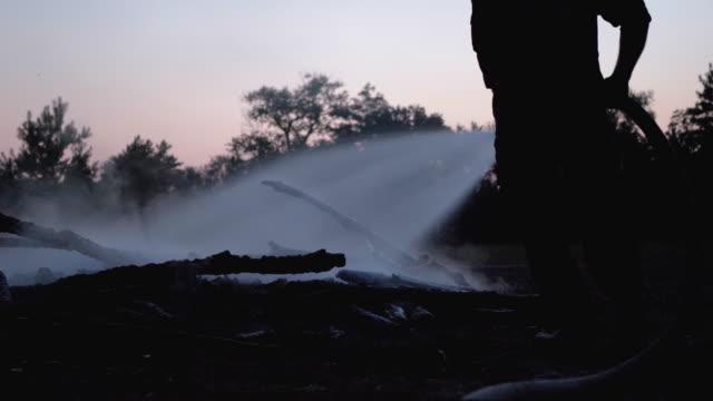 släck eld med vatten genom firehose. brandman håller slang och släcka skogs lägerelden på kvällen - släcka bildbanksvideor och videomaterial från bakom kulisserna