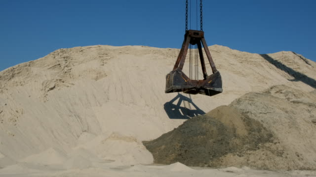Extraction of river sand. Gantry cranes on the riverport loads sand. Delivery of industrial cargo and construction materials by water and freight car. Port cargo cranes with a bucket on the river bank