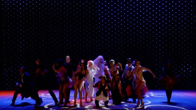 stockvideo's en b-roll-footage met buitengewone mensen in schilderachtige kostuums dansen op het podium in theater - vetschmink