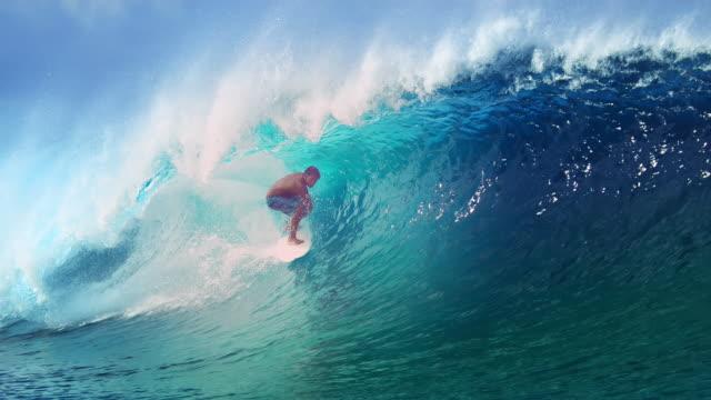 SLOW MOTION: Extreme athlete surfs a big barrel ocean wave glistening.
