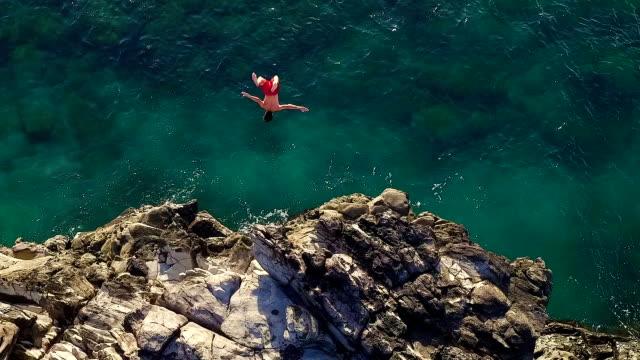 極端懸崖跳躍反轉。鳥懸崖跳入藍海。 - 懸崖 個影片檔及 b 捲影像