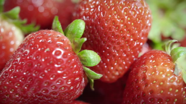 Extreme Close on Pile of Fresh Ripe Organic Strawberries Rotating by Camera video