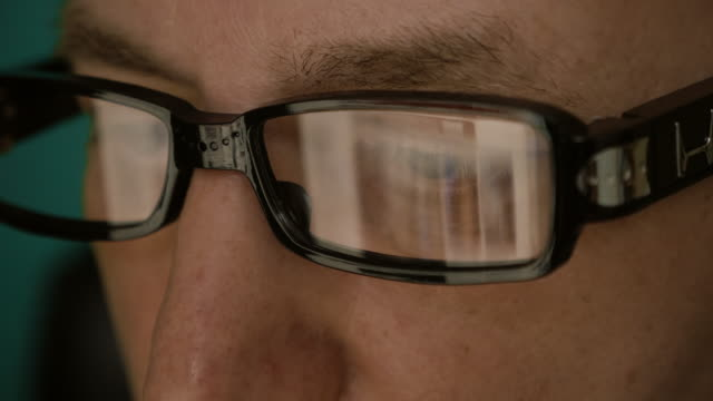 Extreme close up man face eyes glasses. Reflection from computer laptop screen in fashion glasses. Caucasian white man. Man portrait. Surfing internet concept. Extreme close up man face eyes glasses. Reflection from computer laptop screen in fashion glasses. Caucasian white man. Man portrait. extreme close up stock videos & royalty-free footage