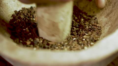 extreme nahaufnahme eines küchenchefs, der getrocknete gewürze mit mörtel und stößel mahlt - kräuter stock-videos und b-roll-filmmaterial