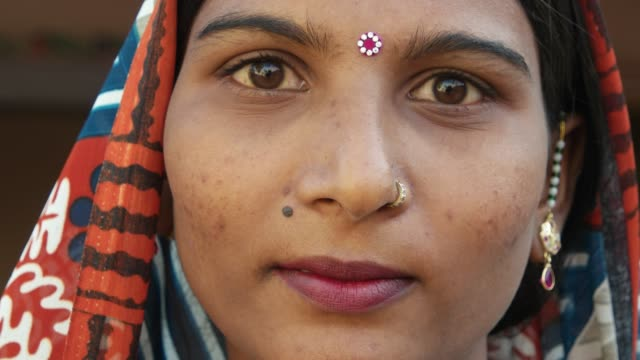 vídeos de stock e filmes b-roll de extreme close up of a gorgeous indian woman's face smiling laughing happy joy jovial looking at camera in traditional dress head covered bindi pretty jewelry at home freedom love static shot lock down - cultura indiana