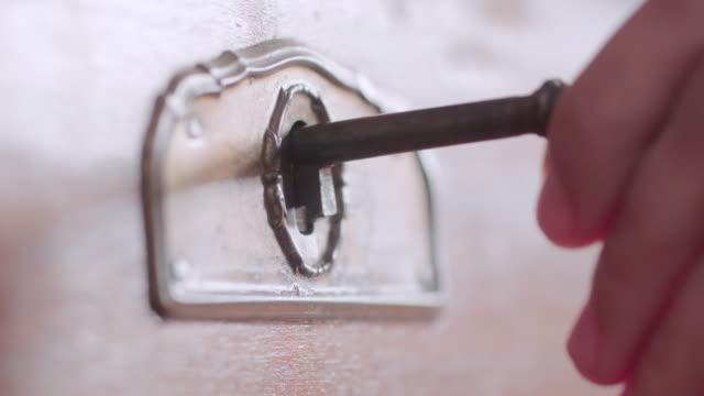 extrem närbild av en hand låsa upp en gammal toffer med en nyckel. - lås bildbanksvideor och videomaterial från bakom kulisserna