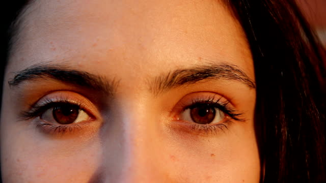 Extreme close up of a woman opens her eyes and smiles.