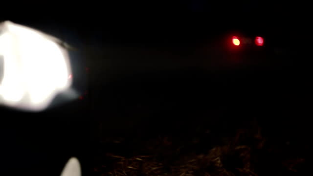 Extreme close up of car headlight at night street. Blurry dark highway with bokeh car lights going by. Background shot video