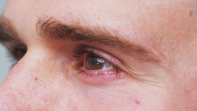 extrem närbild av ögat som man ler i studion sköt från sidan - male eyes bildbanksvideor och videomaterial från bakom kulisserna