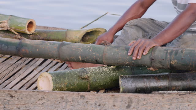 extreme close up on a man sawing bamboo stalk in a dugout canoe