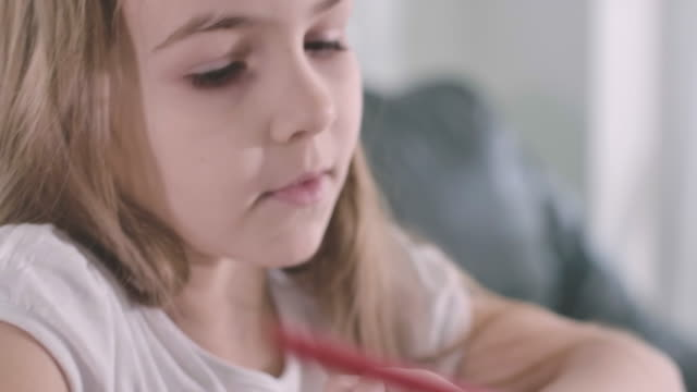 Extreme close-up face of beautiful Caucasian girl writing and talking. Smart serious schoolchild doing homework. Portrait of generation Z children. Intelligence, education. Cinema 4k ProRes HQ.