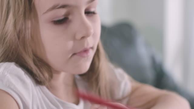 güzel beyaz kızın yazıp konuşmasının aşırı yakın çekim yüzü. akıllı ciddi bir okul çocuğu ev ödevi yapıyor. nesil z çocukların portresi. zeka, eğitim. sinema 4k prores hq. - çalışma kitabı stok videoları ve detay görüntü çekimi