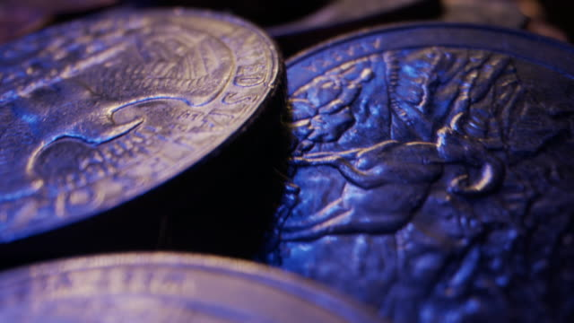 Extreme Close-Up Macro Moving Slider Shot of American Currency Coins Piled Up on a Wooden Table