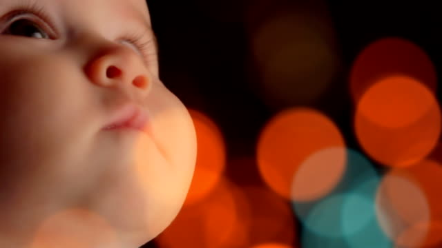 Extreme Close-Up of a Baby HD, studio shot,Extreme Close Up, 5 month old baby girl profile in slow motion 60fps, camera on dolly, selective focus. Defocused light in foreground. brightly lit stock videos & royalty-free footage