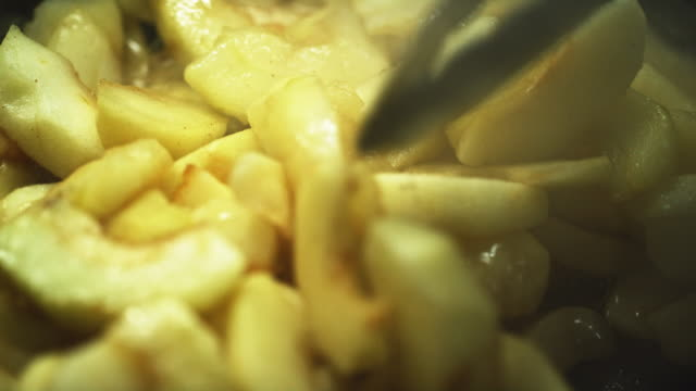 Extreme Close-Up of a Person Using Metal Tongs to Stir Peeled and Sliced Apples in a Bubbling Pan on a Stove Extreme Close-Up of a Person Using Metal Tongs to Stir Peeled and Sliced Apples in a Bubbling Pan on a Stove peeled stock videos & royalty-free footage