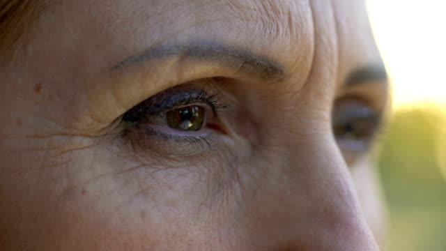 Extreme close-up of mature woman eyes, sad retired lady looking into camera