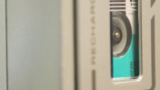 vídeos y material grabado en eventos de stock de extremo primer plano de las bobinas de la grabadora de microcassette girando, marco derecho - disco audio analógico