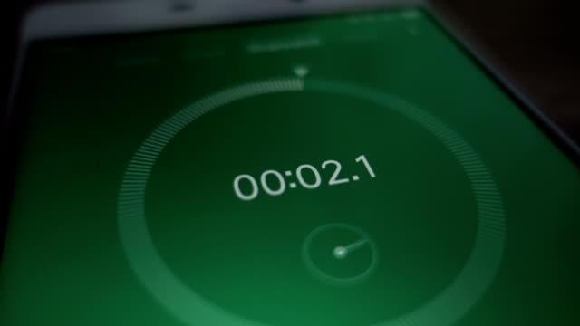 vidéos et rushes de plan rapproché extrême du green du chronomètre numérique avec les nombres blancs de fonctionnement. chronomètre sur l'écran du smartphone. - chrono sport