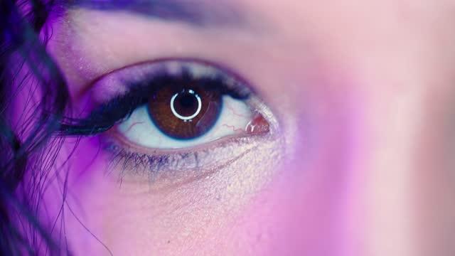 primo primo sguardo estremo dell'occhio umano di iris woman in neon lighting. concetto di vita notturna - flirtare video stock e b–roll