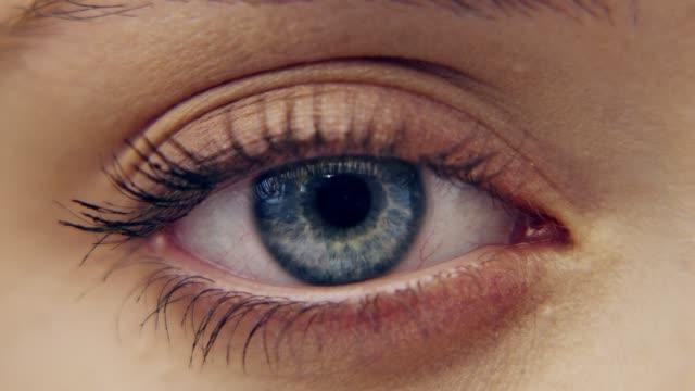 экстремальный крупным планом на ярко-голубой глаз. красивое женское лицо - близко к стоковые видео и кадры b-roll