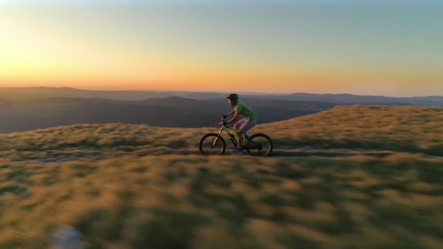 AERIAL: Extreme cross country cyclist speeds along a mountain trail at sunrise.