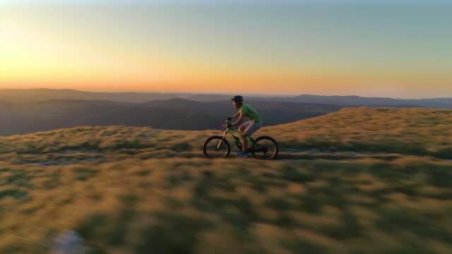 vidéos et rushes de antenne: extrême cross country cycliste accélère le long d'un sentier de montagne au lever du soleil. - moto sport