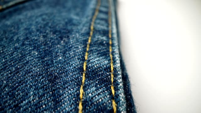 Extreme detailed of blue denim jeans texture in dolly shot over cloth surface.