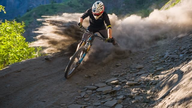 Extreme downhill mountain biker on dirt road making a turn, leaving a cloud of dust behind