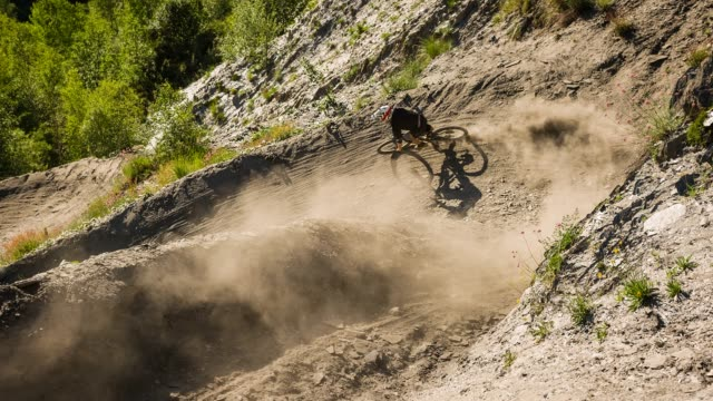 extreme downhill mountain biker on dirt road making a turn, leaving a cloud of dust behind - percorso per bicicletta video stock e b–roll