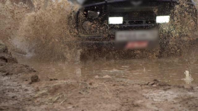 vídeos de stock e filmes b-roll de extreme driving conditions in the countryside. a powerful suv drives into a deep puddle. flying splashes and dirt. beautiful car in rough terrain - estrada em terra batida