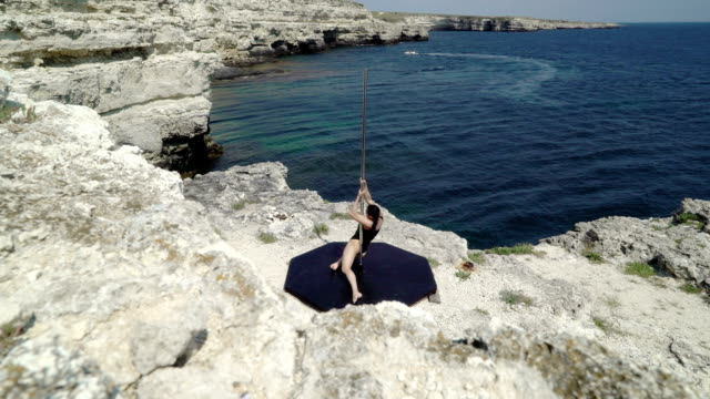 Extreme fitness pole dance workout on a cliff above the sea Extreme fitness pole dance workout on a cliff above the sea young woman using portable stand alone pole stage performing acrobatic tricks on the edge of rock leotard stock videos & royalty-free footage