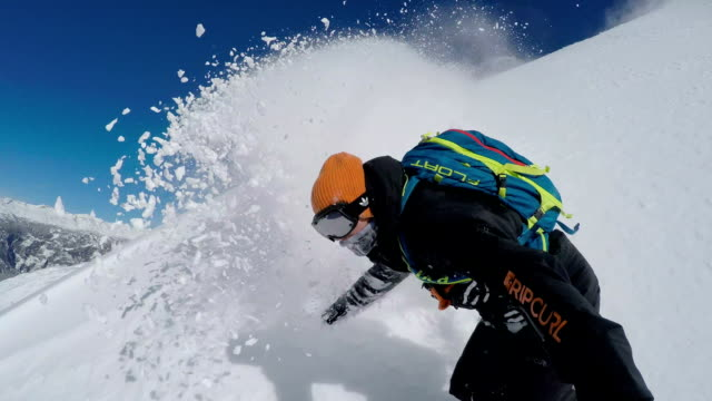 selfie: extreme freeride snowboarder doing powder turns off-piste in mountains - snowboarding video stock e b–roll