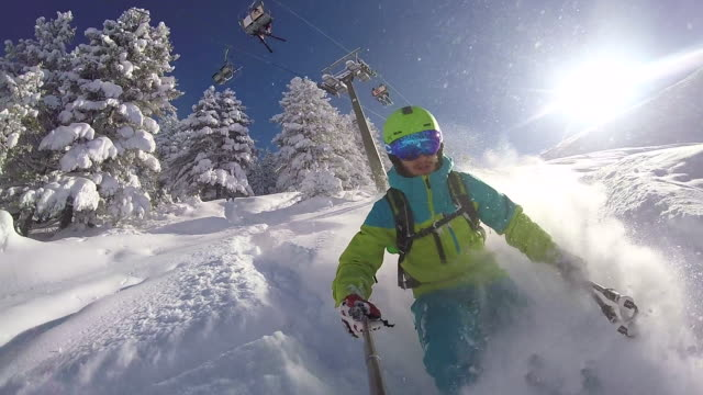 slow motion: extreme freestyle skier riding fresh powder snow in sunny mountains - sci video stock e b–roll
