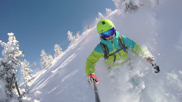 slow motion: extreme freestyle skier skiing fresh powder snow in snowy mountains - sci video stock e b–roll