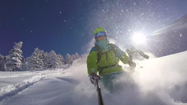 slow motion: extreme freestyle skier skiing fresh powder snow in sunny mountains - sci freestyle video stock e b–roll