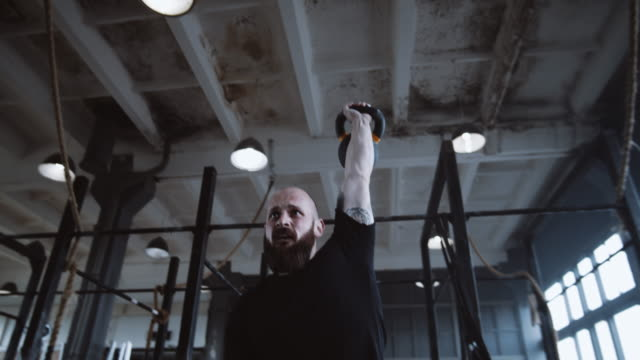 extreme functional training, athletic young caucasian man during workout lifting kettlebell in large gym slow motion. - giria filmów i materiałów b-roll