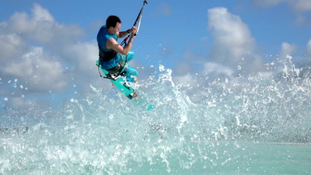 SLOW MOTION CLOSE UP: Extreme kiteboarder jumping and falling into ocean video