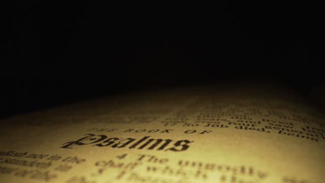 extreme macro close-up moving slider shot of scripture focusing on the book of psalms title in the christian bible in king james translation with red letters for the word of god on a dark background with unique lighting - ветхий завет стоковые видео и кадры b-roll
