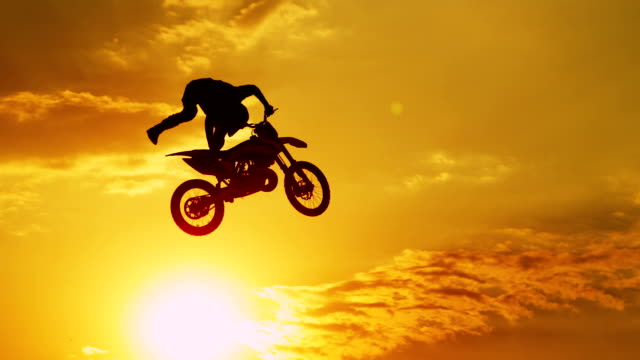 slow motion closeup: extreme motocross biker jumping freestyle trick at sunset - freestyle motocross video stock e b–roll