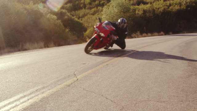 Extreme Motorcyclist Riding Sport Bike on Turn on a Curvy Road With Lens Flare Filmed In Slow Motion Low angle of extreme man on motorcycle making tight turn on road by camera motorcycle stock videos & royalty-free footage