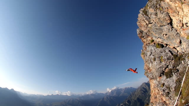 extreme parachute jump from the top of the mountain. - base jumping video stock e b–roll