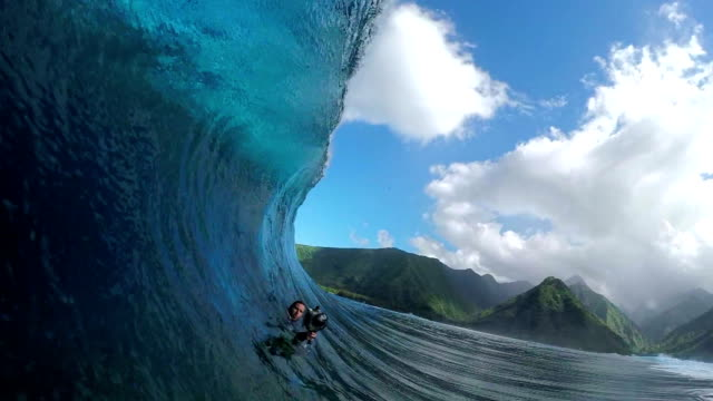 SLOW MOTION: Extreme photographer filming pro surfer riding tube wave video
