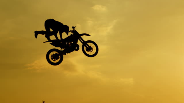 slow motion: extreme pro motocross biker jumping freestyle trick over the sun - motocross video stock e b–roll