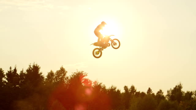 slow motion: extreme pro motocross biker jumps dusty big air kicker over the sun - freestyle motocross video stock e b–roll