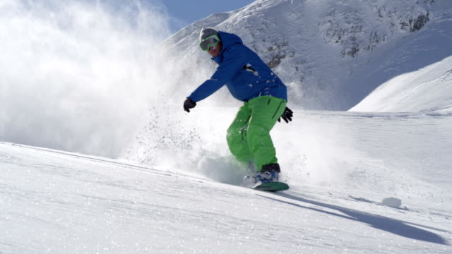 slow motion: extreme snowboarder doing powder turn in fresh mountain snow - snowboarding video stock e b–roll
