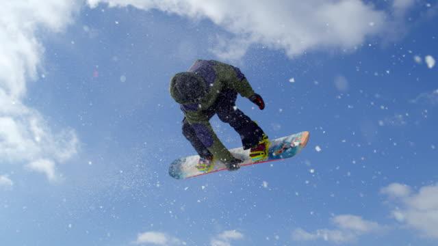 замедленная съемка крупным планом : экстрим сноуборде, прыжки воздухе кикер в солнечный зимний парк в снегу в горы - сноубординг стоковые видео и кадры b-roll