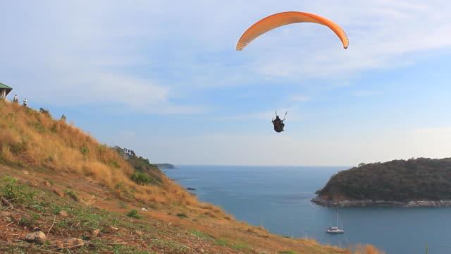 экстремальные виды спорта: полеты на параплане над морем прозрачный небесно-голубой - парапланеризм стоковые видео и кадры b-roll