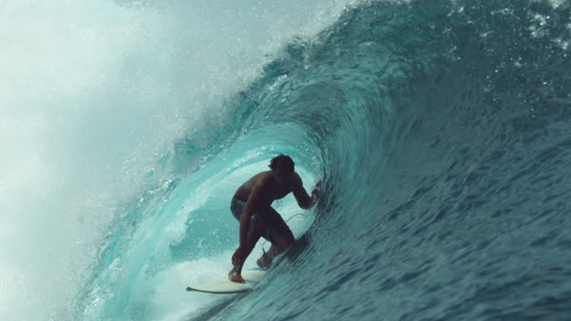 vídeos de stock e filmes b-roll de slow motion: extreme sportsman having fun riding a beautiful barrel ocean wave. - desportista