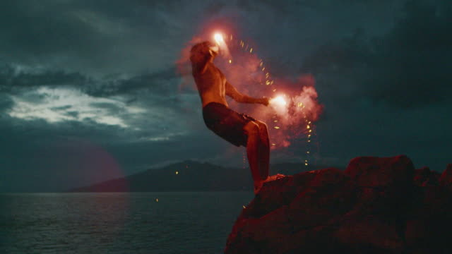Extreme stuntman does a backflip with fire into the sea Extreme cliff jumping man backflipping off of an sea cliff with burning red hot flares at night, epic stuntman moments, people are awesome cliff jumping stock videos & royalty-free footage